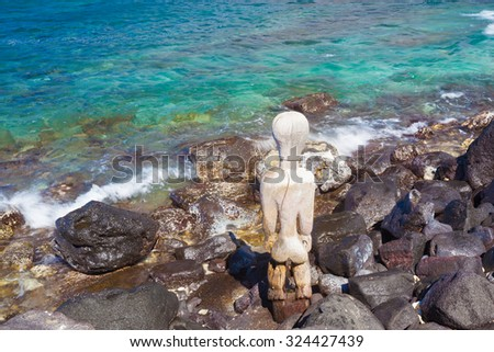 Old wooden protection idol facing the ocean at an ancient Hawaiian site Pu'uhonua O Honaunau National Historical Park on Big Island, Hawaii - stock photo