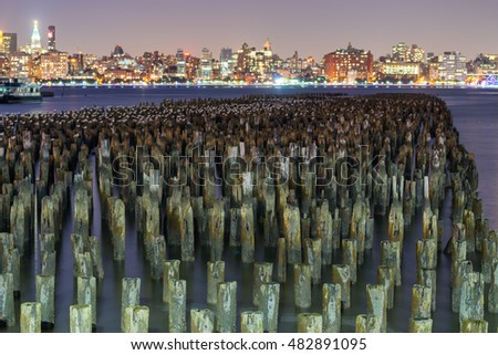 Old wooden pylons in Brooklyn, New York City at night.
