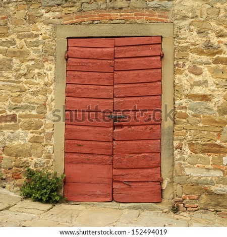 old wooden red gate and stonewall, detail of historic tuscan building, Italy, Europe - stock photo