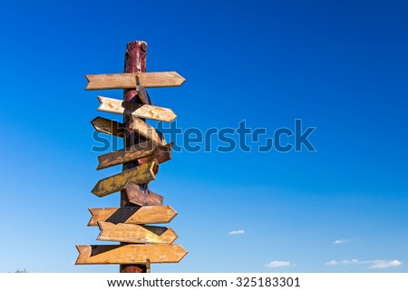 Old wooden road signs with many left and right arrows. - stock photo