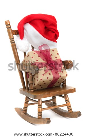 old wooden rocking Chair with red jelly bag cap and christmas present - stock photo