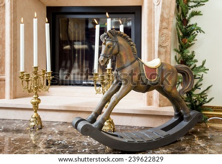 Old wooden rocking horse for children on the background of burning candlesticks in sconces near the fireplace - stock photo