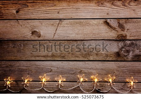 Old wooden rustic Christmas background with star shaped lights.
