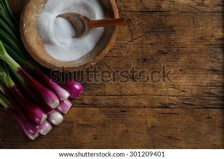 Old wooden salt box with fresh onions near, retro style - stock photo