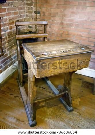 Old wooden school desk in brick wall building - stock photo
