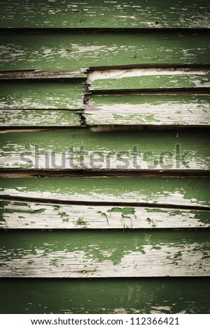 Old wooden siding with peeling green paint. - stock photo