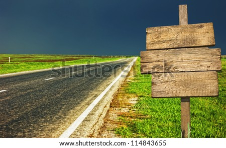 old wooden sign at the country road - stock photo