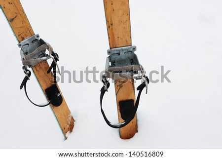 old wooden skis in the snow, horizontal - stock photo