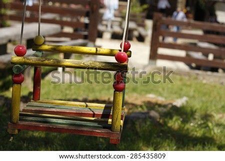 old wooden swing in the backyard - stock photo