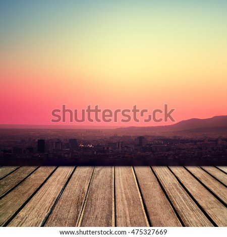 Old wooden table in front of  sunset sky as background. Vintage plank board with beautiful  sunset