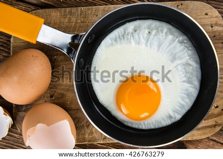 Old wooden table with fried eggs (selective focus; close-up shot) - stock photo