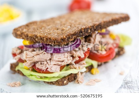 Old wooden table with Tuna sandwich (on wholemeal bread; selective focus)