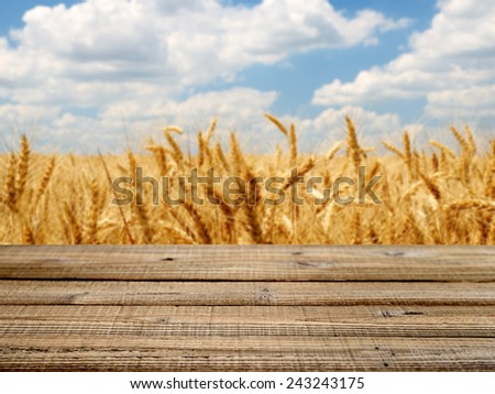 Old wooden table with wheat field background. Shallow depth of field - stock photo