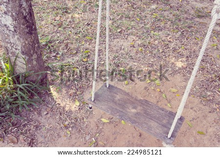 Old wooden tree swing with dry leaf background - stock photo