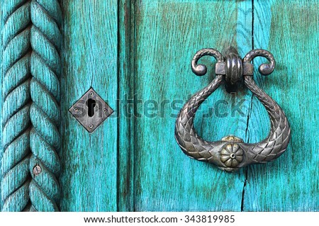Old wooden turquoise door  with aged metal door handle. Architectural textured background  - stock photo