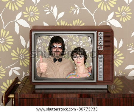 old wooden tv with nerd silly couple retro in screen on wallpaper background [Photo Illustration] - stock photo