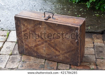 Old wooden vintage suitcase standing on a brick coating at a grass background