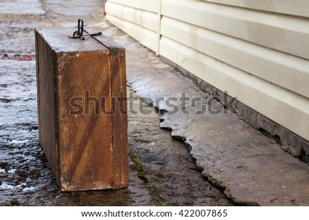 Old wooden vintage suitcase standing on the wet ruined concrete coating - stock photo