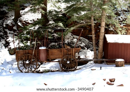 Old wooden wagon and shack in the snow - stock photo