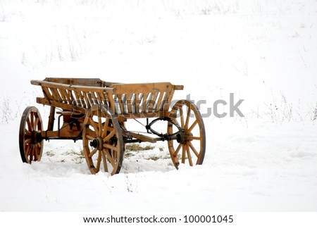 old wooden wagon in the snow in a field - stock photo