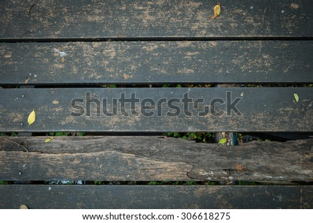 old wooden walkway with falling leaves in the morning of autumn seasonal - stock photo