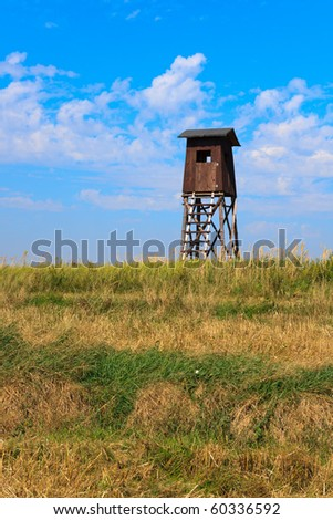 Old wooden watch tower in a field stubble with blue sky background - stock photo