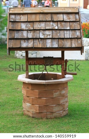 Old wooden well and bucket of water inside on grass ground, primitive knowhow - stock photo