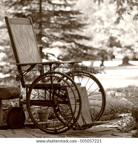 Old wooden wheelchair sits waiting in the garden - stock photo