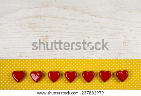 Old wooden white background with seven red hearts on the yellow frame with white dots. - stock photo