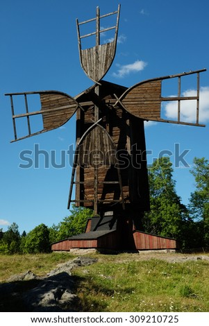 old wooden windmill against the blue sky - stock photo