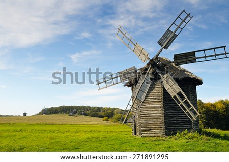 old wooden windmill in a field