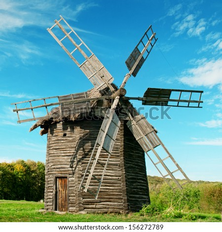 Old wooden windmill in the background of the autumn forest - stock photo