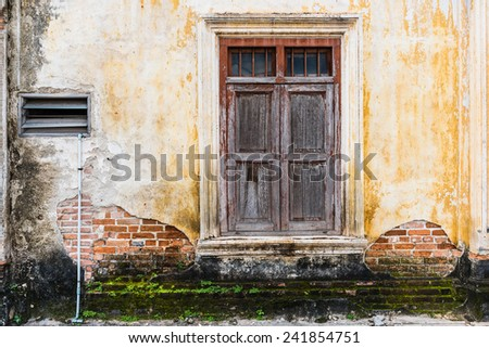 Old wooden window on the cracked brick wall - stock photo