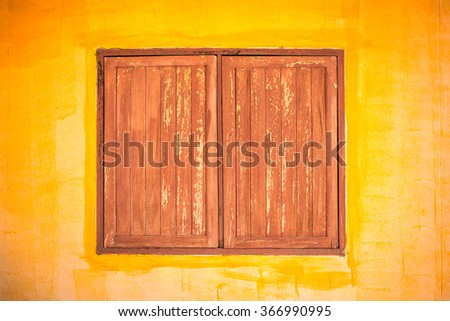 Old wooden window on yellow wall - stock photo