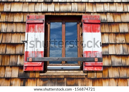 Old wooden window with shutters in the national colors of Austria