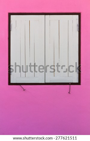 Old wooden windows closed on a white concrete wall in a house beautifully pink. - stock photo