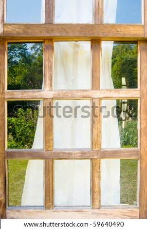 Old wooden windows with drape and reflect sky and grassland - stock photo