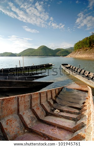 Old woody boat, lake and mountain in blue sky background