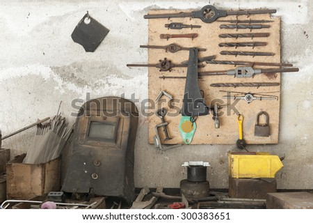 old workbench with old work tools hanging on wall garage - stock photo