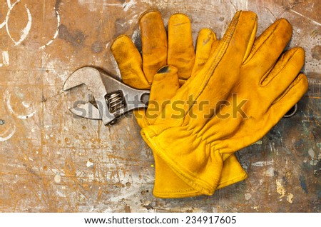 Old workbench with spanner and two yellow work gloves on worn surface. - stock photo