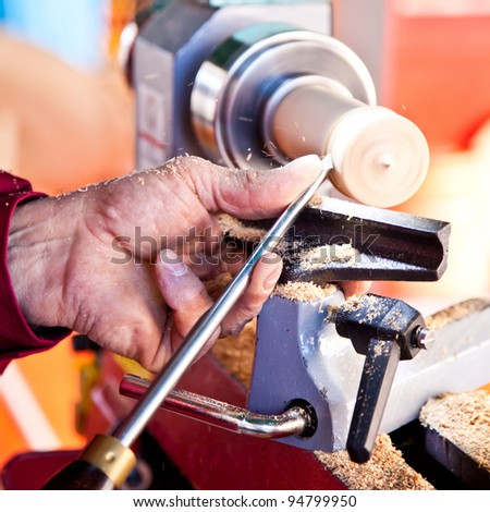 Old worker hands at lathe - stock photo