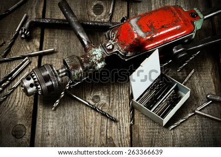 Old working tools. A drill with drills on a wooden background. - stock photo