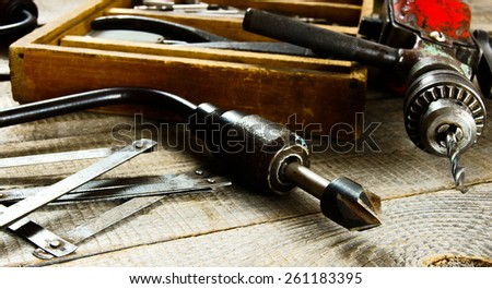 Old working tools. Drills in a box, a drill, a chisel on a wooden background.