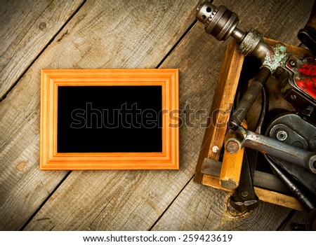 Old working tools. Frame with old tools (drill, mallet, saw and others) in a box on a wooden background. - stock photo