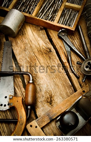 Old working tools. Vintage working tools (saw, plane, pliers and others) on wooden background. - stock photo