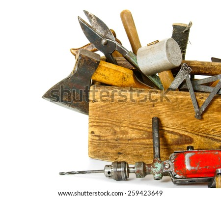 Old working tools. Working tools (drill, axe, saw and others) in an old box on white background. - stock photo