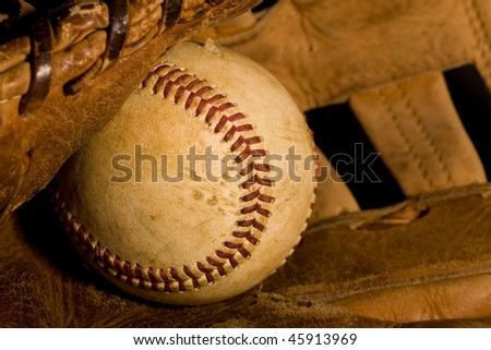 Old worn baseball sitting in ragged glove in a closeup view. - stock photo
