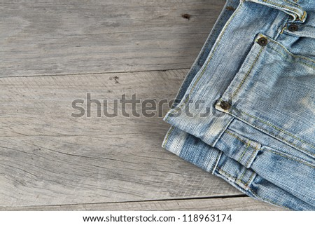 Old worn blue jeans over an old wooden background