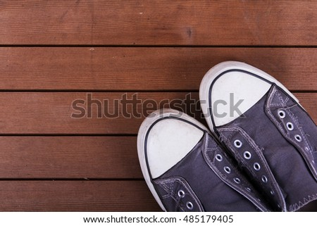 Old worn canvas shoes on a wooden floor