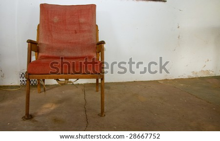 old worn chair against dirty white wall